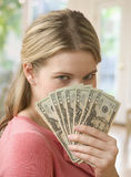 Woman Holding Cash. A young woman is holding up cash as a fan while obstructing her face.  Verticalshot Stock Photos