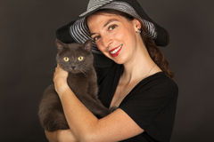 The woman is holding the cat in her arms Stock Image