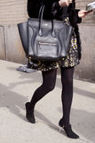 A woman holding a Celine handbag.