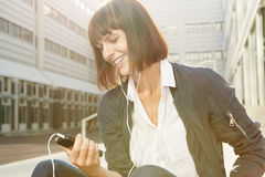 Woman holding cellphone and listening to music with earphones Stock Image
