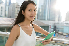 Woman holding cellphone and smile to camera in the city. Asian young woman Stock Photo