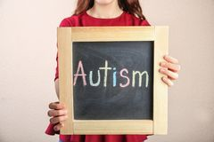 Woman holding chalkboard with word AUTISM. On light background Stock Image