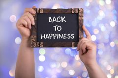 Back to happiness. A woman holding chalkboard with words back to happiness on bokeh light background royalty free stock photos