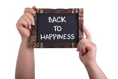 Back to happiness. A woman holding chalkboard with words back to happiness isolated on white background royalty free stock images