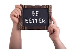 Be better. A woman holding chalkboard with words be better isolated on white background royalty free stock photography