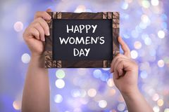 Happy women`s day. A woman holding chalkboard with words happy women`s day on bokeh light background stock photo