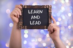 Learn and lead. A woman holding chalkboard with words learn and lead on bokeh light background Royalty Free Stock Photos