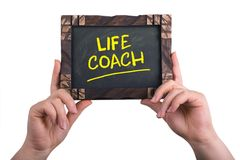 Life coach. A woman holding chalkboard with words life coach on white background stock photos
