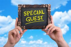 Special guest. A woman holding chalkboard with words special guest on blue sky background Royalty Free Stock Photo