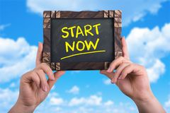 Start now. A woman holding chalkboard with words start now on blue sky background Stock Photo