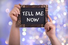 Tell me now. A woman holding chalkboard with words tell me now on bokeh light background Royalty Free Stock Photos