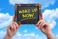 Wake up now sign. A woman holding chalkboard with words wake up now on blue sky background Stock Photo