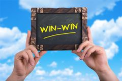 Win win. A woman holding chalkboard with words win win on blue sky background Stock Photos