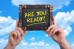 Are you ready. A woman holding chalkboard with words are you ready on blue sky background Royalty Free Stock Images