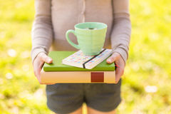 Woman holding chamomile tea and stacked books Stock Photos