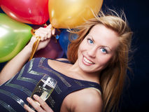 Woman holding champagne and balloons Stock Photos