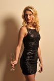 Woman holding champagne. Blonde woman in a cocktail dress holding a glass with champagne Royalty Free Stock Photos