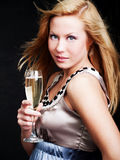 Woman holding champagne over dark Stock Images