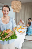 Woman holding chicken roast with family at dining table Royalty Free Stock Photos