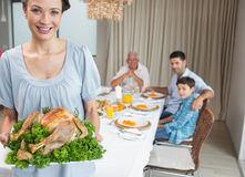 Woman holding chicken roast with family at dining table Stock Image