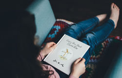 Woman holding child's book on sofa Royalty Free Stock Photos