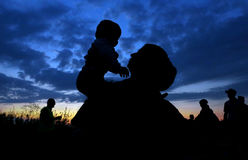 Woman holding a child. In susnset, silhouette Stock Image