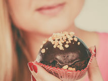 Woman holding chocolate cupcake about to bite Royalty Free Stock Image