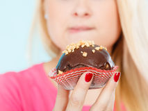 Woman holding chocolate cupcake about to bite Stock Images