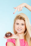 Woman holding chocolate cupcake about to bite Stock Image