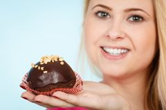 Woman holding chocolate cupcake about to bite Stock Photo