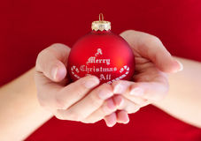 Woman holding christmas ball. Woman in red holding red christmas ball Royalty Free Stock Photo