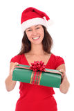 Woman holding christmas gift. Woman in Santa hat holding Christmas gift Stock Image