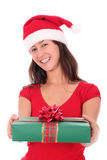 Woman holding christmas gift. Woman in Santa hat holding Christmas gift Royalty Free Stock Images