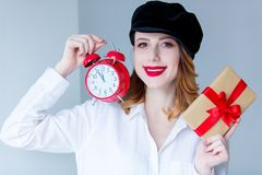 Woman holding christmas gift box and red retro alarm clock Stock Photos