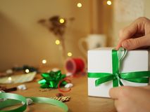 Woman holding Christmas gift with green ribbon royalty free stock photo