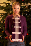 Woman Holding Christmas Gifts In Front Of Tree Royalty Free Stock Image