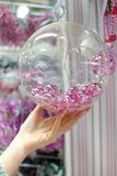 Woman holding Christmas glass bowl with small pink Royalty Free Stock Images