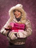 Woman holding a Christmas present.  Royalty Free Stock Images