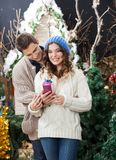 Woman Holding Christmas Present With Man At Store Royalty Free Stock Photos