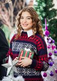 Woman Holding Christmas Present In Store Royalty Free Stock Image