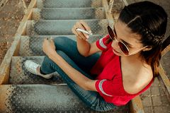 Woman Holding Cigarette Sitting on Stairs royalty free stock photography