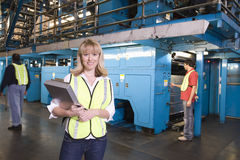 Woman Holding Clipboard With Operators Behind At Factory Royalty Free Stock Photography