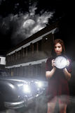 Woman holding clock. Outside a building next to a parked car at night under moonlight Stock Image
