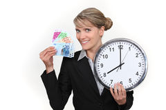 Woman holding clock and bank notes. Business woman holding clock and bank notes Stock Photo