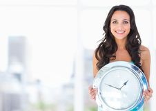 Woman holding clock in front of bright blur Stock Photo