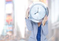 Woman holding clock in front of bright city Royalty Free Stock Photo