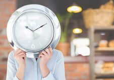 Woman holding clock in front of cafe Royalty Free Stock Photography