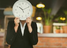 Woman holding clock in front of cafe Stock Image