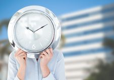 Woman holding clock in front of city buildings Royalty Free Stock Photos
