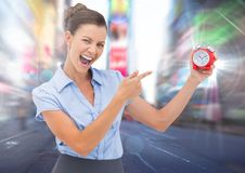Woman holding clock in front of city rush Royalty Free Stock Photos